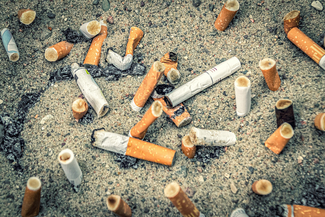 Zigarettenverbot - Zigarettenfilter im Sand